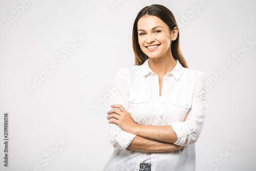 Portrait of happy smiling young beautiful woman, isolated over white background. Looking at camera. Free space for text.
