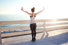 Slim Woman Stretching Up With Arms Wide Open Outdoors By The Sea.