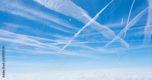 Multiple contrails cross paths through the sky Wallpaper Mural