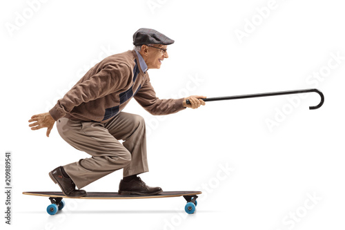 Elderly man riding a longboard and holding a cane