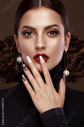 Fotografía Pretty girl with unusual hairstyle, bright makeup, red lips and manicure design