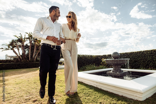 Fototapeta Stylish couple walking outdoors in lawn