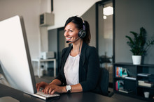 Beautiful Customer Representative With Headset Smiling During Conversation With A Client.