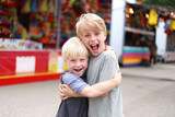 Two Happy Little Boys Hugging and Smiling at Small Town American Carnival