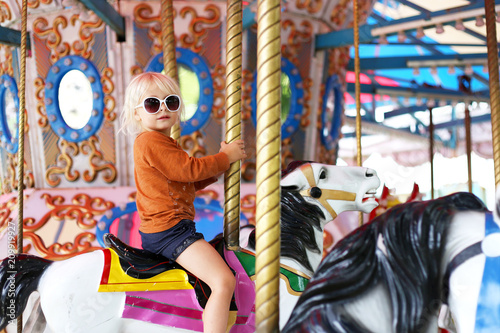 Photo Cute Little Toddler Girl in Big Sunglasses Riding on Carnival Carousal
