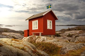 Typisch schwedisches Holzhaus an der Küste mit Fahne