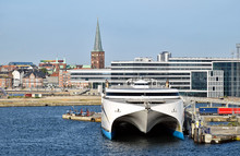 A High-speed Ferry Has Moored In The Harbor Of Aarhus (Denmark). In The Background Modern And Historic Buildings Can Be Seen.