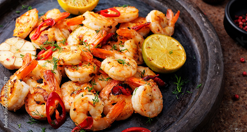Photo  Prawns Shrimps roasted on  pan with lemon and garlic on dark rustic background