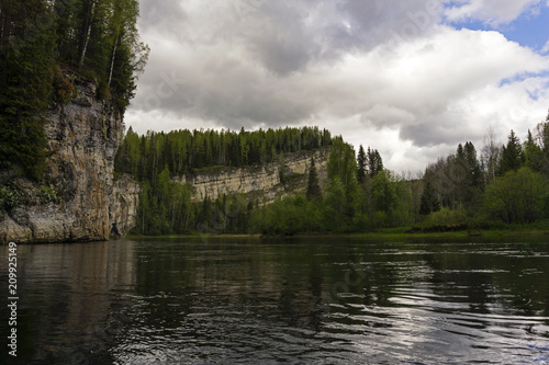 Foto op Canvas Bleke violet landscape - river with beautiful rocks on wooded shores on a cloudy day