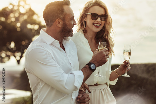 Fotografie, Obraz Smiling couple enjoying a glass of wine
