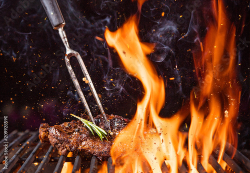 Fotografiet Beef steak on the grill with flames