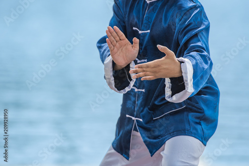 Fotografie, Obraz  Young man practicing traditional Tai Chi Chuan, Tai Ji and Qi gong in the park for healthy, traditional chinese martial arts concept