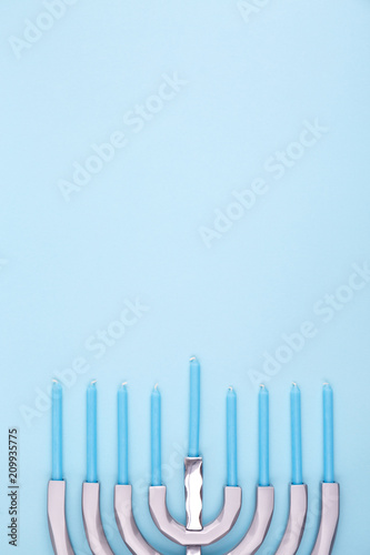 Blue background with menora and candles. Hanukkah and judaic holiday concept.