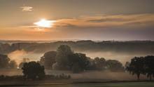 Franken - Wiesengrund Bei Sonnenaufgang Mit Baumkulissen Und Kirche Im Hintergrund