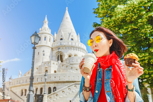 Fototapety, obrazy: Young asian woman tourist drinking frappe sweet cold coffee and tasty muffin at the Budapest city street near Fisherman Bastion. Travel in Hungary and fast food break concept