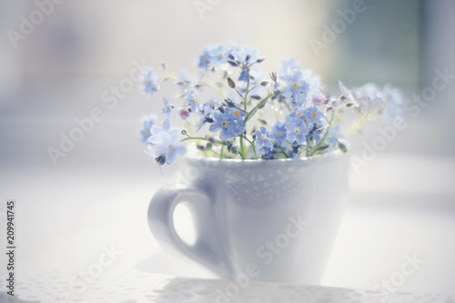 Fototapeta Blue flowers of a forget-me-not in a cup on a lacy tray. obraz na płótnie