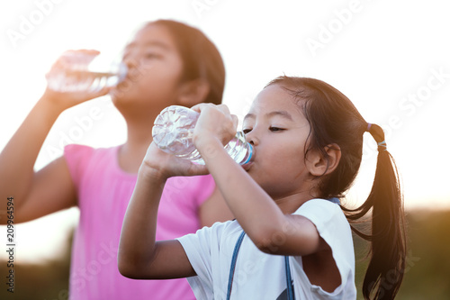 Photo Cute asian little child girl drinking fresh water from bottle with her older sis