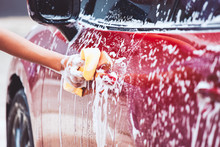 Man Washing Red Car With Sponge And Soap
