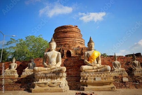 Tuinposter Bedehuis Travel Thailand - Buddha statue in Wat Yai Chaimongkol on blue sky and cloud background, Ayutthaya Historical Park. The brick pagoda at old ayutthaya temple ruins. Space for text in template.
