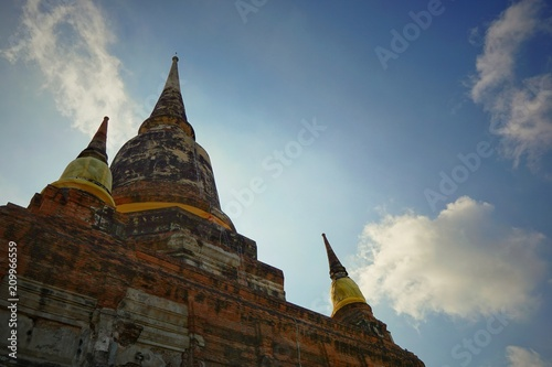 Staande foto Bedehuis Travel Thailand - Pagoda and brick wall in Wat Yai Chaimongkol on blue sky and cloud background, Ayutthaya Historical Park. The brick pagoda at old ayutthaya temple ruins. Space for text in template.