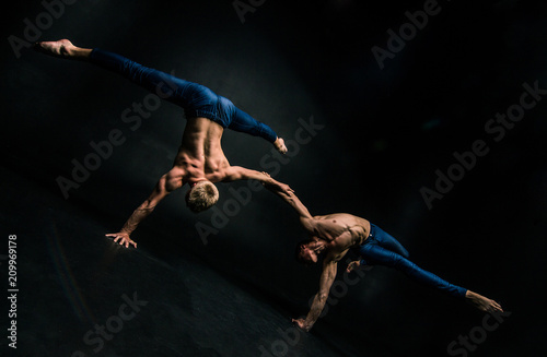 Photo  Male acrobatic duo performs a complicated balancing act on a dark background