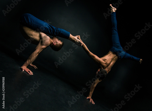 Male acrobatic duo performs a complicated balancing act on a dark background Poster