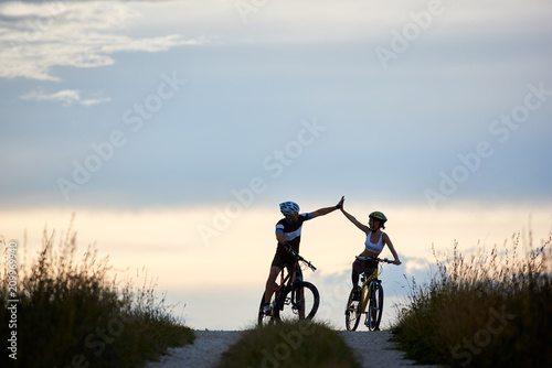 Sporty woman and man wearing sportswear and helmets, riding bicycles, having fun outside. Silhouettes of sportsmen highing five and posing on road in sunset time. Non urban scene.