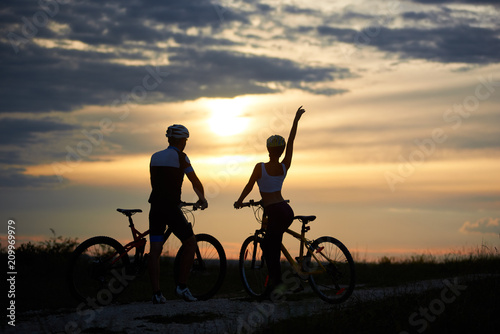 Fotografia  Rear view of a couple of cyclists standing with bicycles and enjoying the sunset