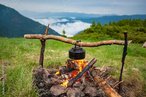 Fototapeta Old small kettle is heated on a bonfire