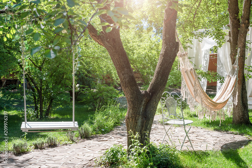 Poster Jardin Wooden swing on ropes and hammock under the big tree in the garden.