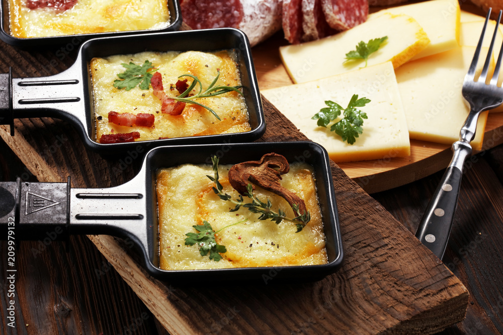 Fototapeta Delicious traditional Swiss melted raclette cheese on diced boiled or baked potato.