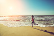 Fitness woman running by the beach at sunrise. Healthy active lifestyle girl exercising outdoors