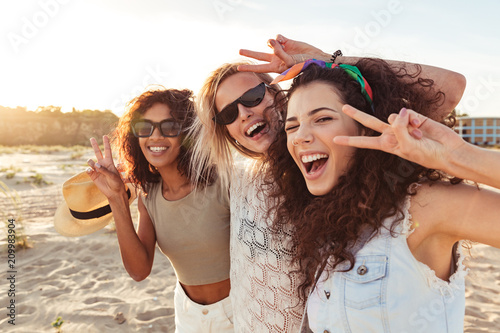 Foto  Image of three funny multiethnic girls 20s in summer clothing laughing and showi