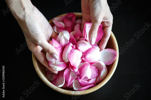 Staande foto Macrofotografie Close-up macro photo of woman's hands with rose petals, wooden bowl on a black table