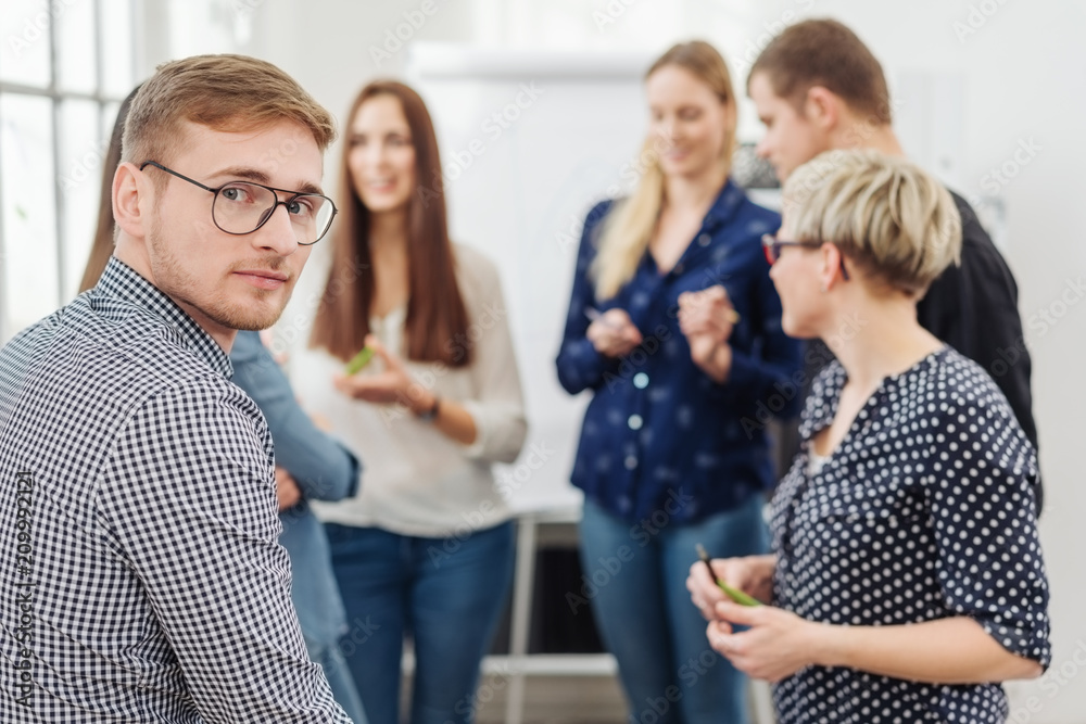 Fototapeta Portrait of young man in office team meeting