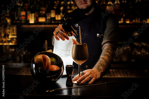 Valokuva  Bartender adding cocktail from the syphon to the copper cup