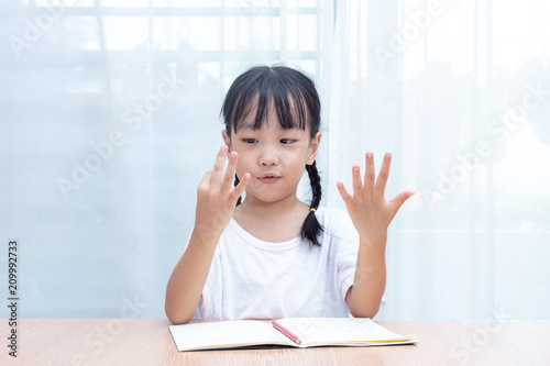 Valokuva Asian little Chinese Girl doing mathematics by counting fingers