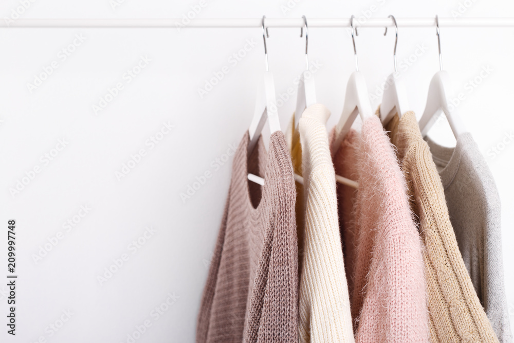 Fototapety, obrazy: Warm knitted, autumn, winter clothes hanging on a rack, trending concept, pastel colors