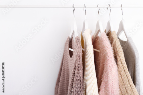 Fototapeta Warm knitted, autumn, winter clothes hanging on a rack, trending concept, pastel colors obraz