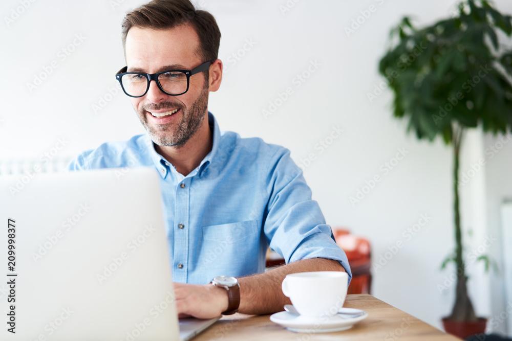 Fototapeta Handsome man at cafeteria, cafe working on laptop