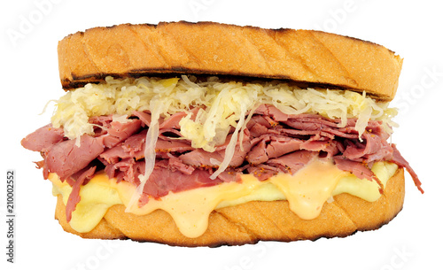 Pastrami Reuben style sandwich with sauerkraut and Swiss cheese isolated on a white background