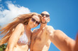 Beautiful young funny couple doing selfie on the shore of the tropical sea. Vacation, travel, freedom, happiness and joy.