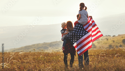 Obraz happy family with flag of america USA at sunset outdoors - fototapety do salonu