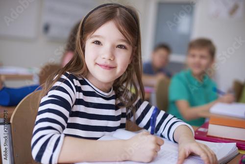 Portrait of smiling schoolgirl writing in exercise book in class