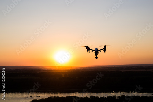 Staande foto Helicopter silhouette of drone, quadrocopter with photo camera flying in the sky.