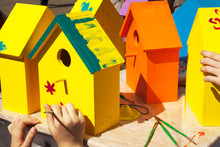 Children Painting Birdhouses Bright Colors Of Orange And Yellow. Kids Woodcraft Lesson, Making Wooden Houses For Birds