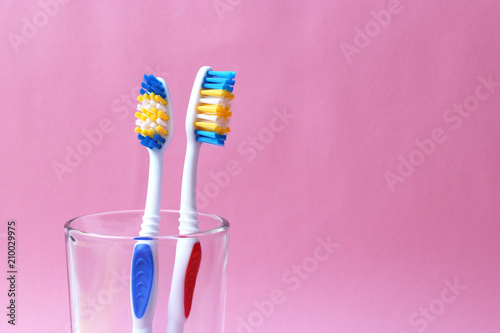 Fotografía toothbrushes in a glass on a colored background
