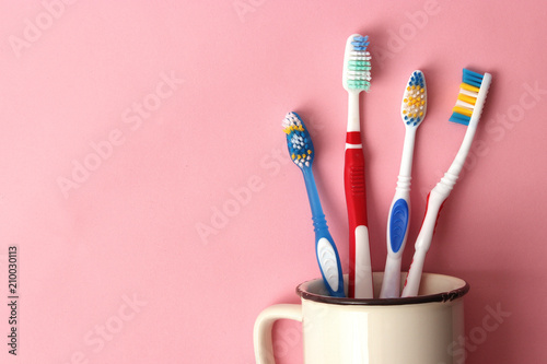 Valokuva  toothbrushes in a glass on a colored background