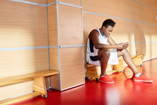 African-American Man In Basketball Uniform Sitting Browsing Smartphone And Enjoying Good Music While Sitting On Bench In Gym.