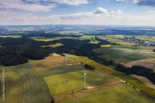 Green fields and forests landscape with wind power plants - bird eye perspective Fotobehang